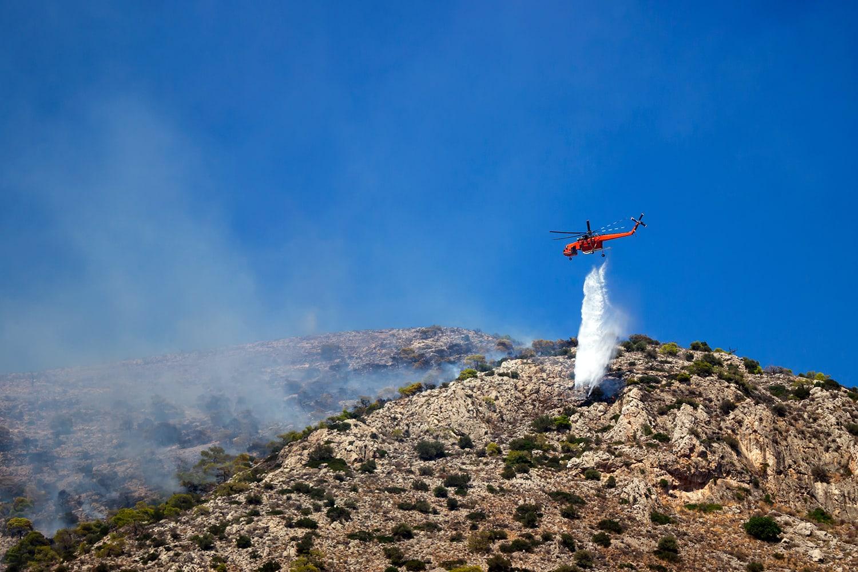 Un elicottero combatte contro le fiamme, durante gli incendi in Grecia